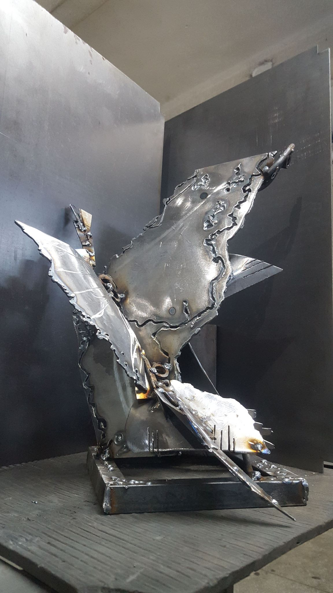 Iron metal sculpture with nice reflections contrast on surfaces representing an abstract versonal version of a flying bird